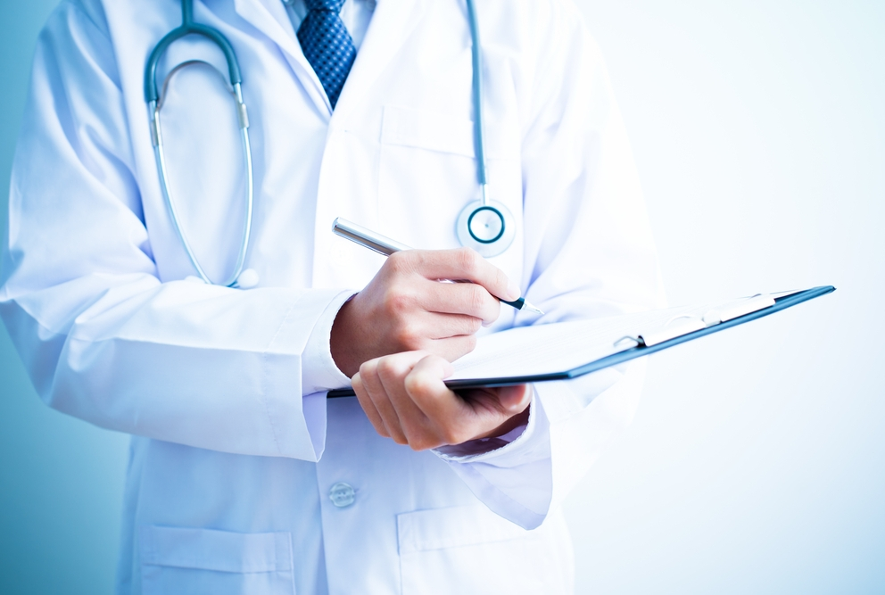 Male doctor filling out a checklist
