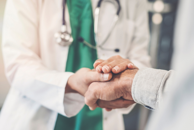 Photo of doctor holding patient's hand